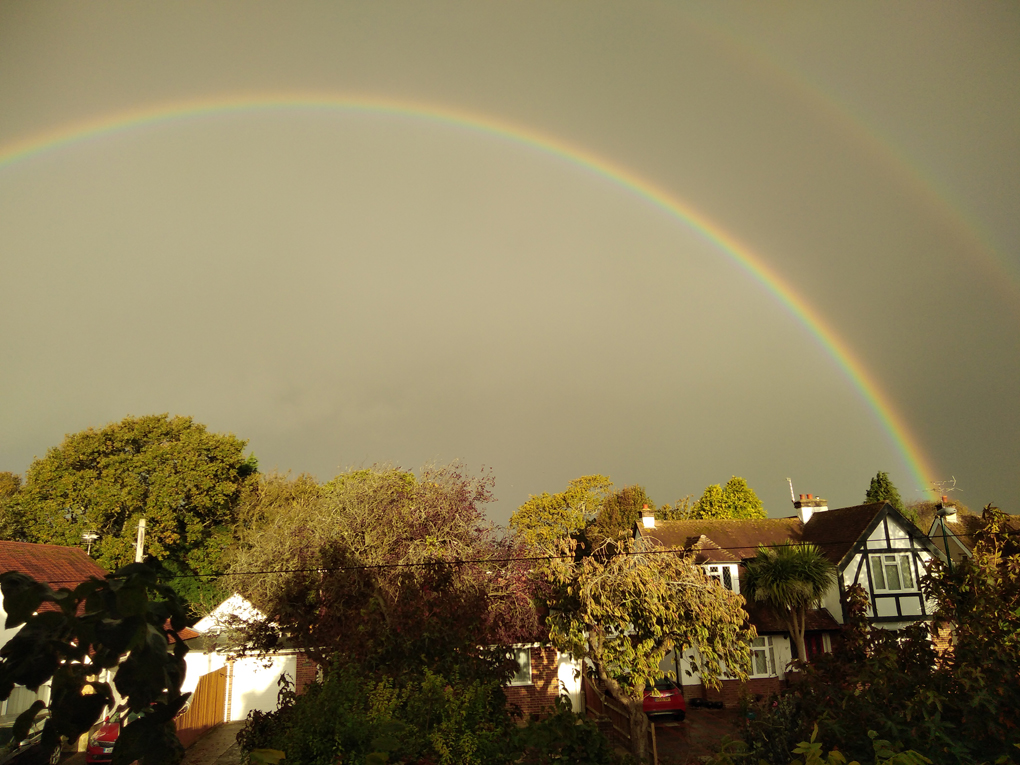 A rainbow arches over houses and trees against a background of a very dark sky