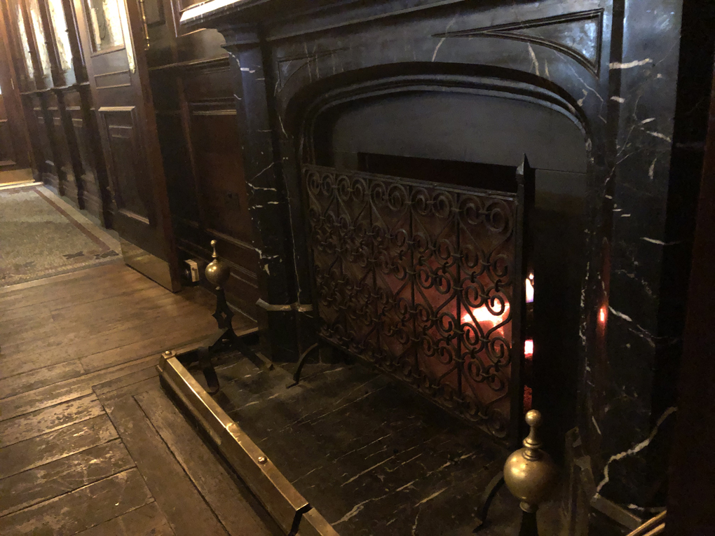 Open fire in fireplace in wooden panelled room
