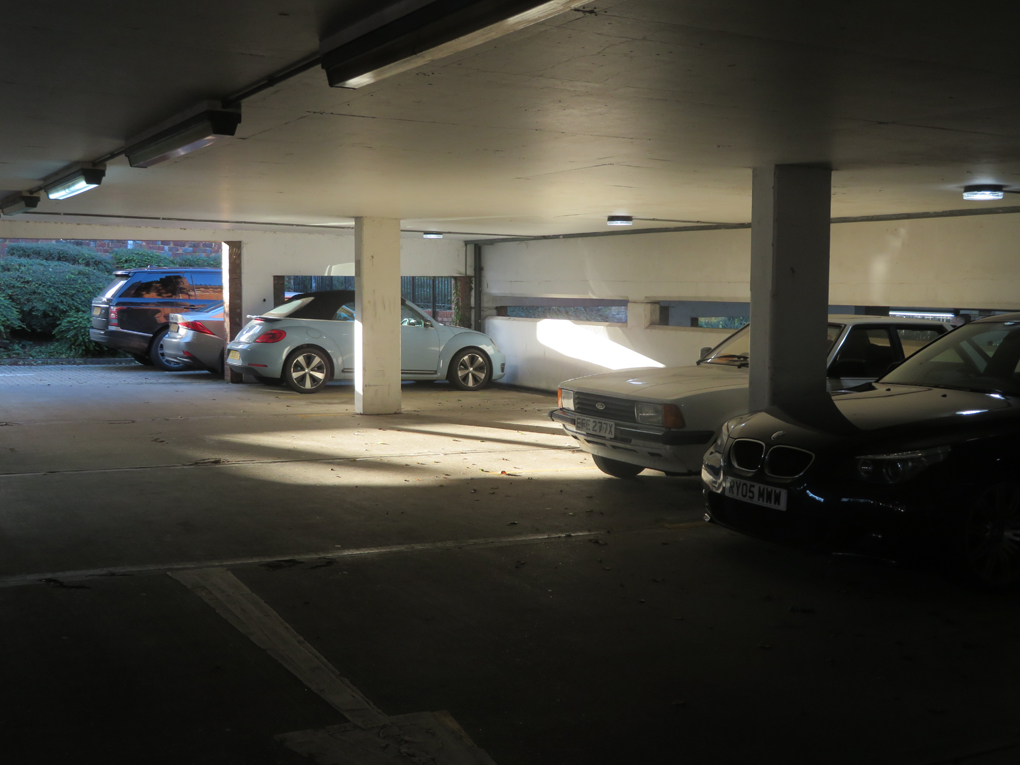 A shaft of late Autumn sunlight brightly illuminates a spot in an a below ground car park in St Martins car park Dorking