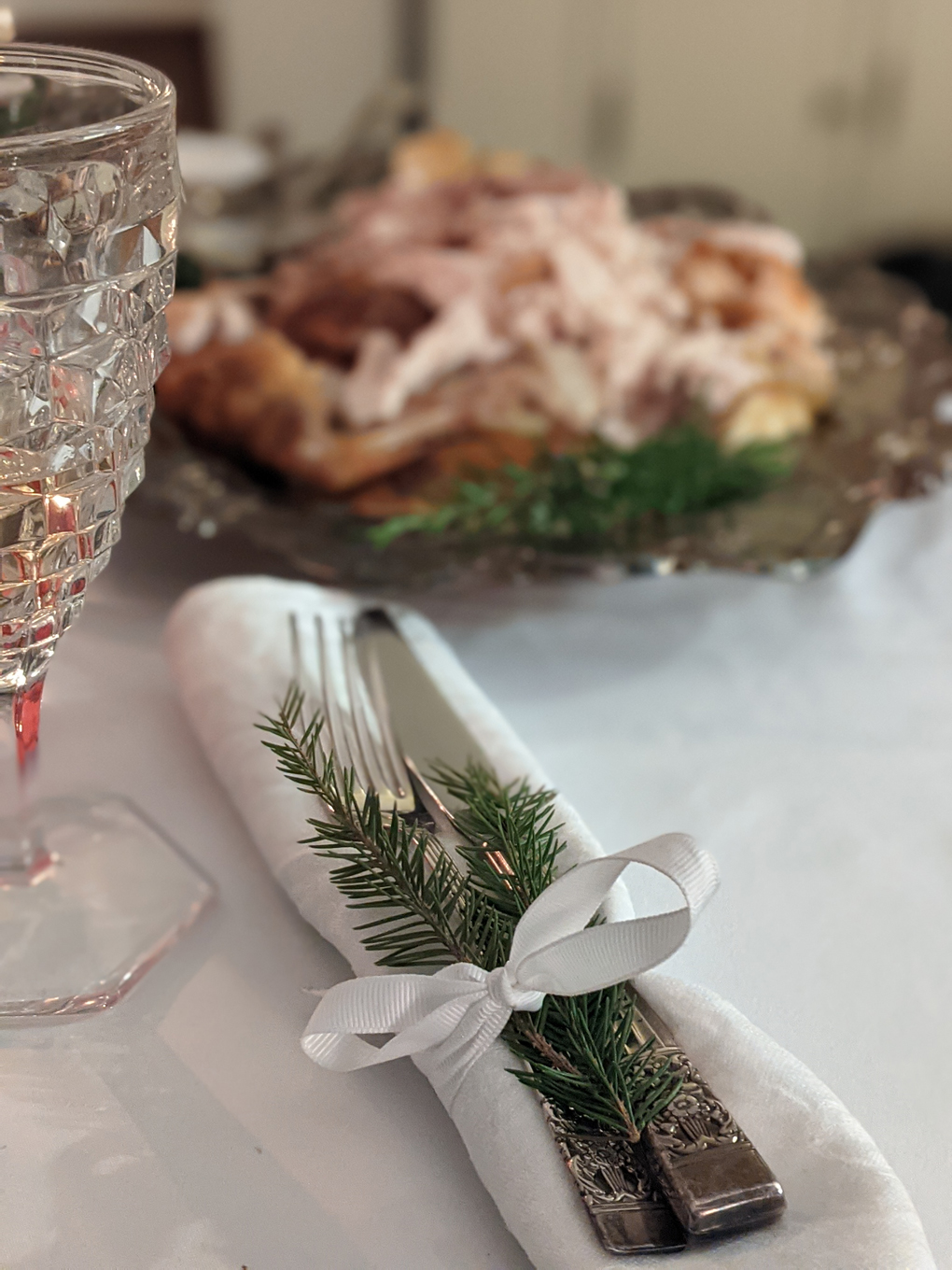 Cutlery wrapped in napkin with festive foliage, blurred platter of turkey in background