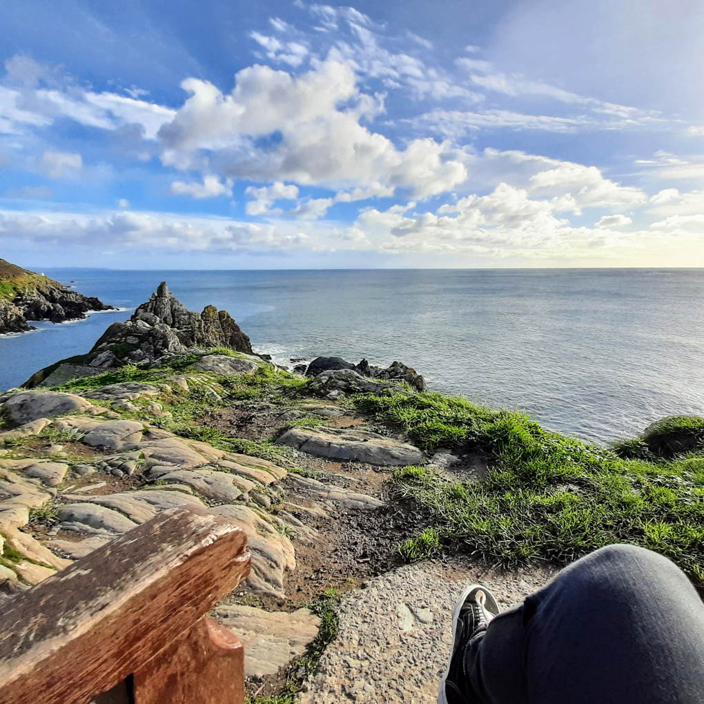 A view from a bench at the top of a dramatic cliff with jagged rocks leading to a bright calm sea and sky.