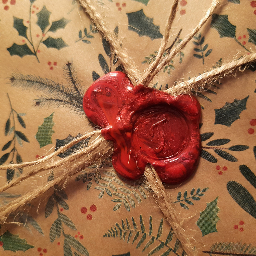 A red wax seal with a letter J stamped onto Christmas wrapping paper