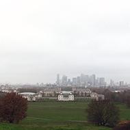 Photograph overlooking the historic buildings and university in Greenwich with London shrouded by fog in the distance.