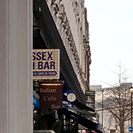 Part of a shop sign with the left side obscured to reveal the apparent sign 'Sex Bar'.