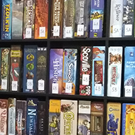The corner of a room filled with shelves of many different board games, chair and table with menu on.