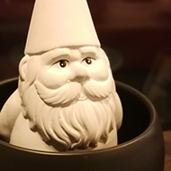 white gnome sitting in a small bowl