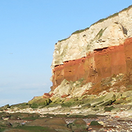 the red and white cliffs of Hunstanton, with a blue sky frame the beach which is covered in large boulders.
