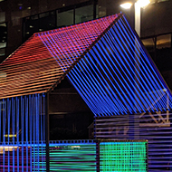 A set of geometric shapes and structures covered in colourful, flourescent wires.