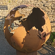 A rusty old globe of metal approx 3 1/2ft in diameter, set on a smaller cylindrical tube of the same. The map of the world had been cleverly cut out in the surface of the globe, the rust illuminated in the sunlight. Cool concept for a sculpture!