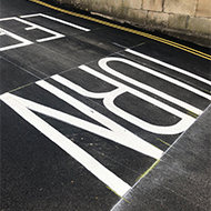The words 'Turn left' painted in large white letters on a black road
