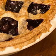 A blueberry pie looking pretty damn amazing except for some ragged edges on the crust where it kind of looks like a critter trying to escape being devoured by a slime monster