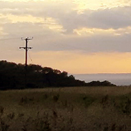 Dark storm clouds out to sea overlaying a bright sunset, viewed from a hillside