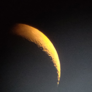 A hazy crescent moon viewed through a telescope