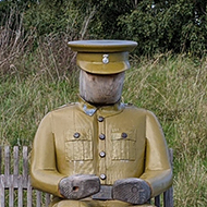 Bench with a life-size wooden figure of a soldier sitting at one end.