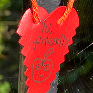 A paper heart has been tied to a metal gate. The text 'hi friend!' is written on the heart with a drawing of a smiling apple.