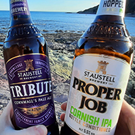 Two hands holding beer bottles of Tribute and Proper Job ale on a rocky beach with the sea in the background