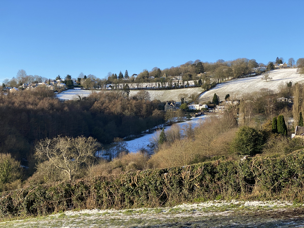 A view of hills, fields and trees, all lightly dusted with snow, under a clear sky