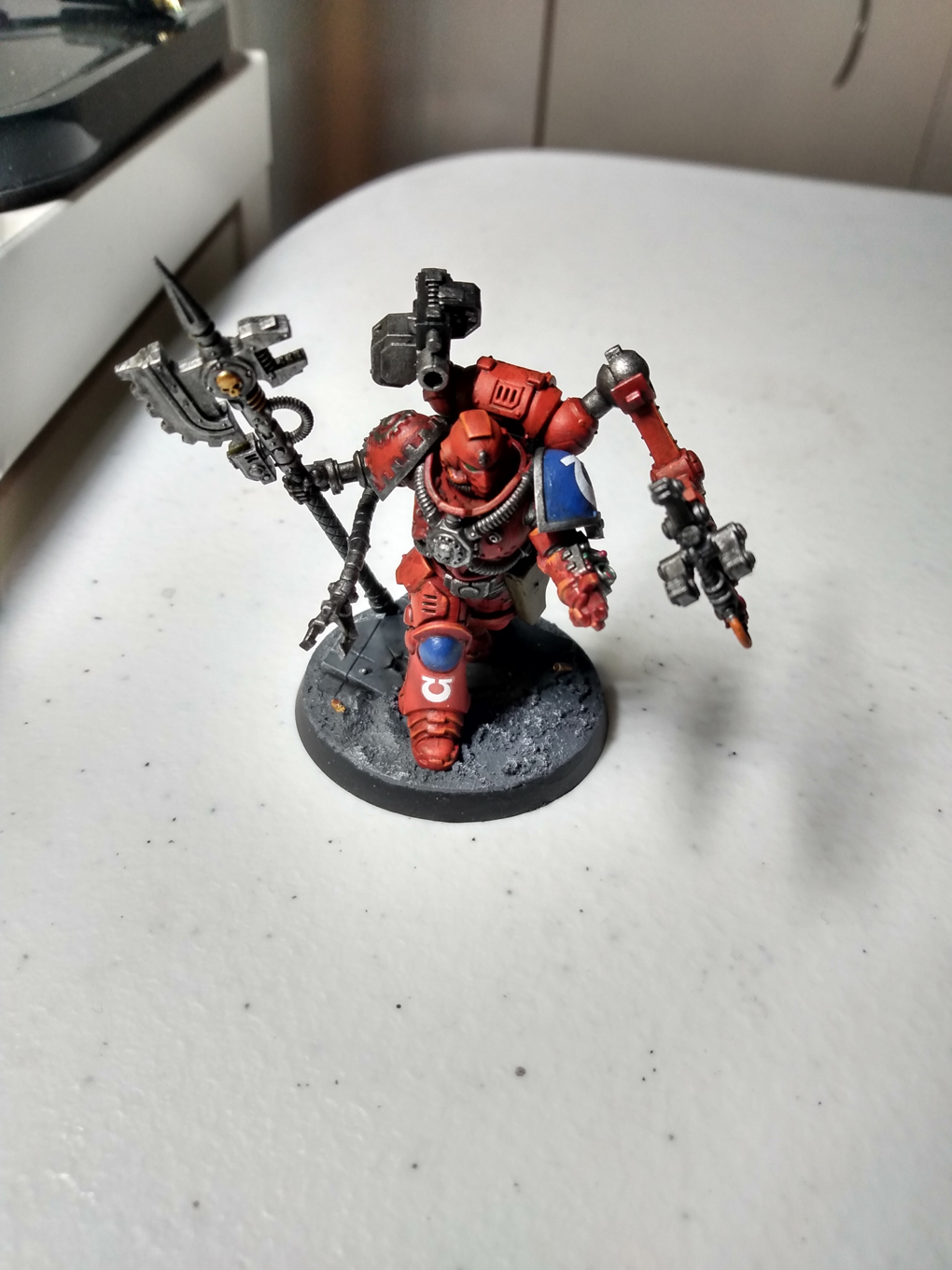 A red armoured space marine miniature sits of a table