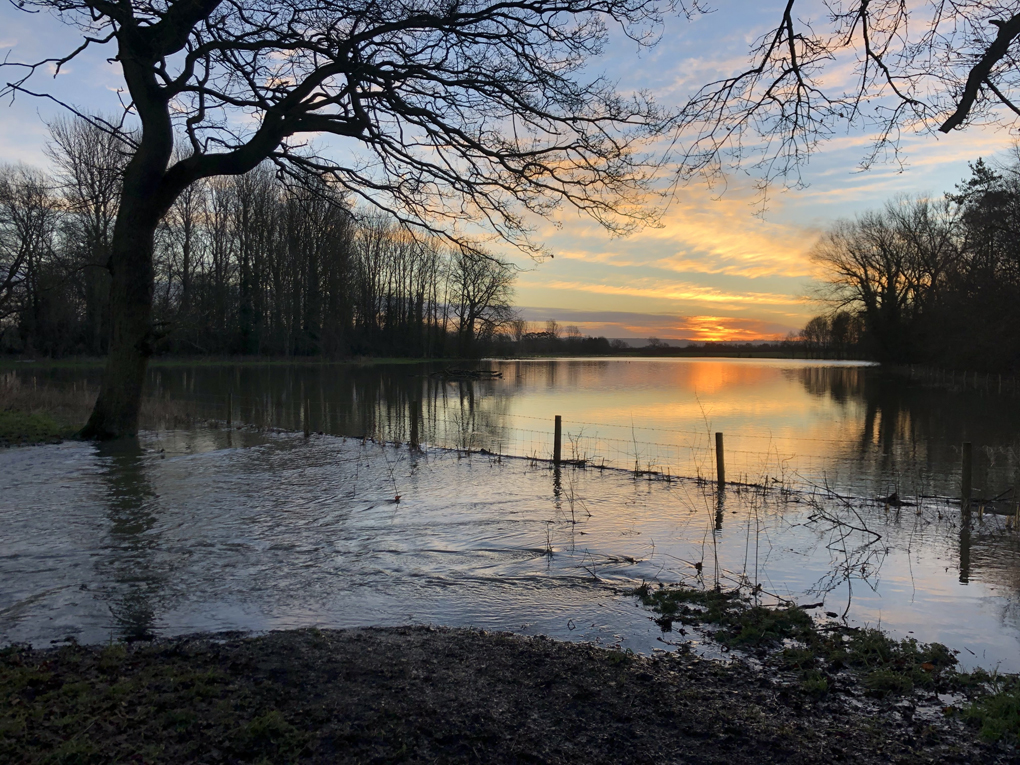 Sunrise over a flooded field, with water flowing from the field across a footpath in the foreground.
