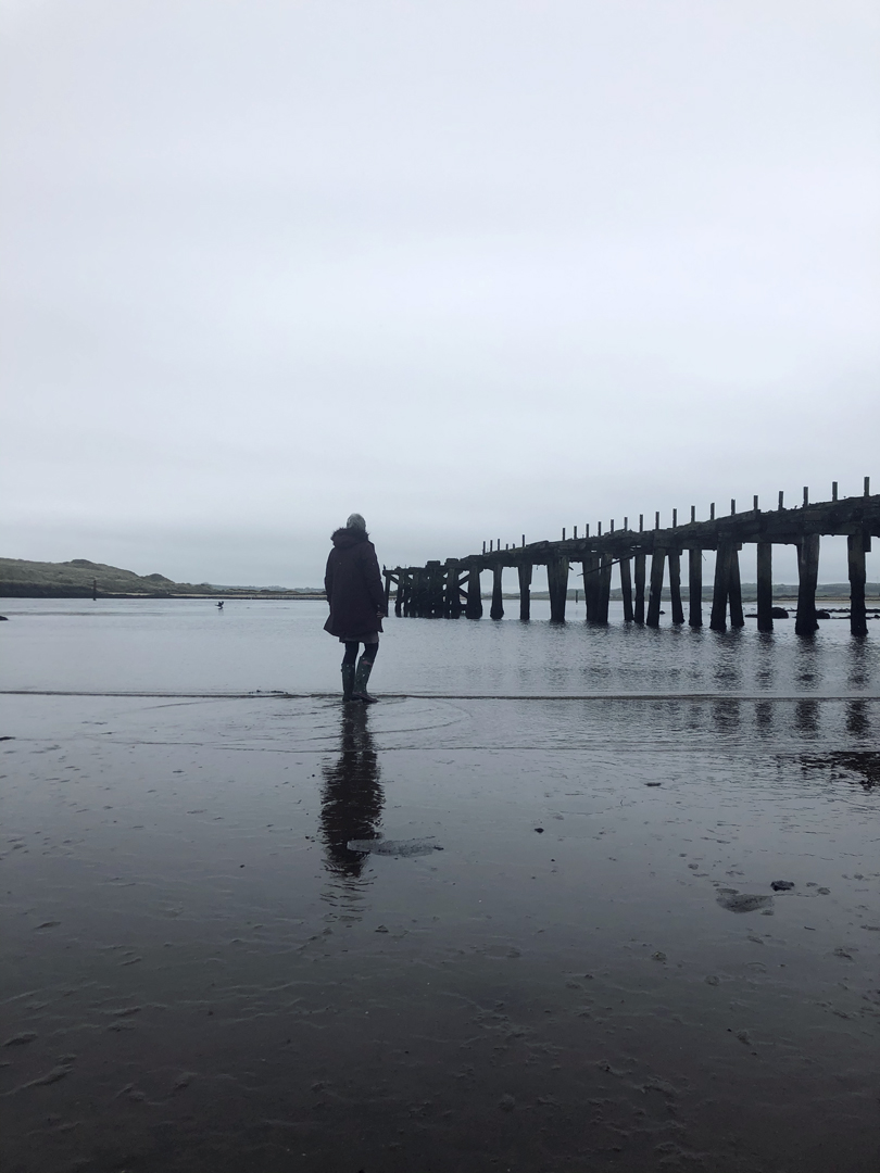 A woman overlooking an estuary with rail bridge ruins silhouetted against the grey waters and skies.